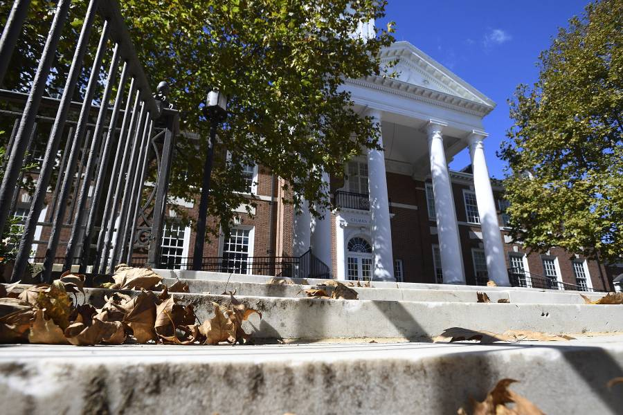 Exterior of Gilman Hall with fall leaves on the marble steps