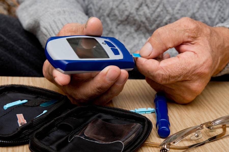 An elderly person monitors his blood sugar using a glucose monitor