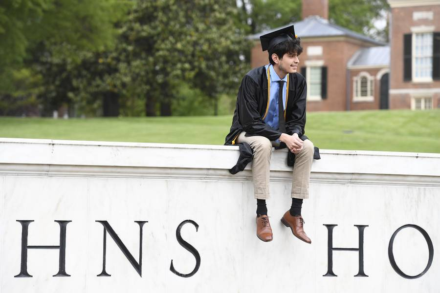 Graduate sits on the Johns Hopkins gateway sign