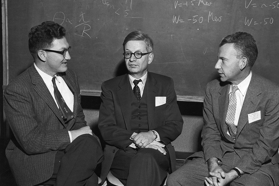 Black and white photo: Three men chat in front of a blackboard with mathematical equations