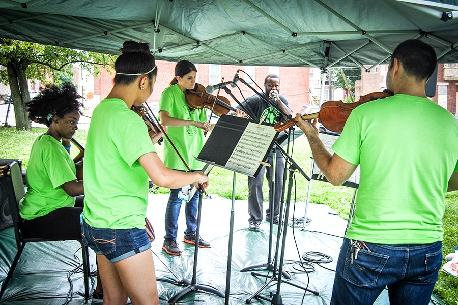String quartet players in lime green t-shirts perform under a tent