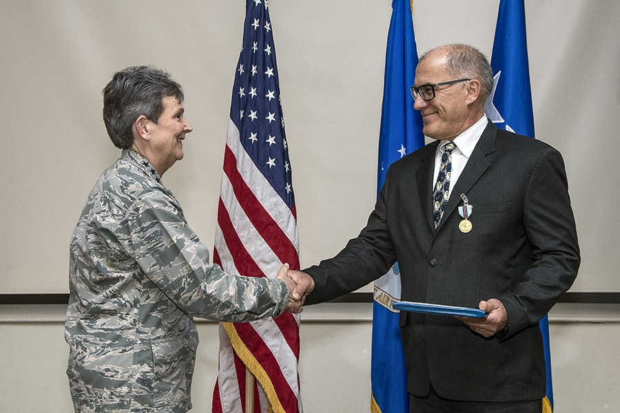 A woman in army fatigues shakes the hand of a man in a suit who is holding a plaque