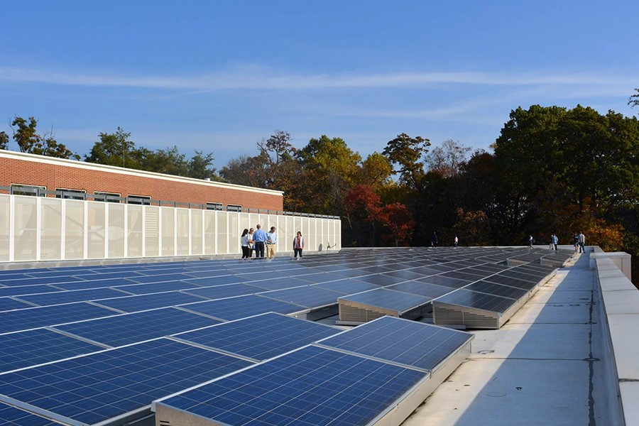 Multiple rows of solar panels line a roof while a small tour group walks