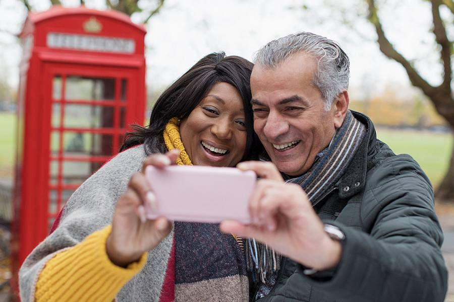 Senior man and woman taking selfie in a park