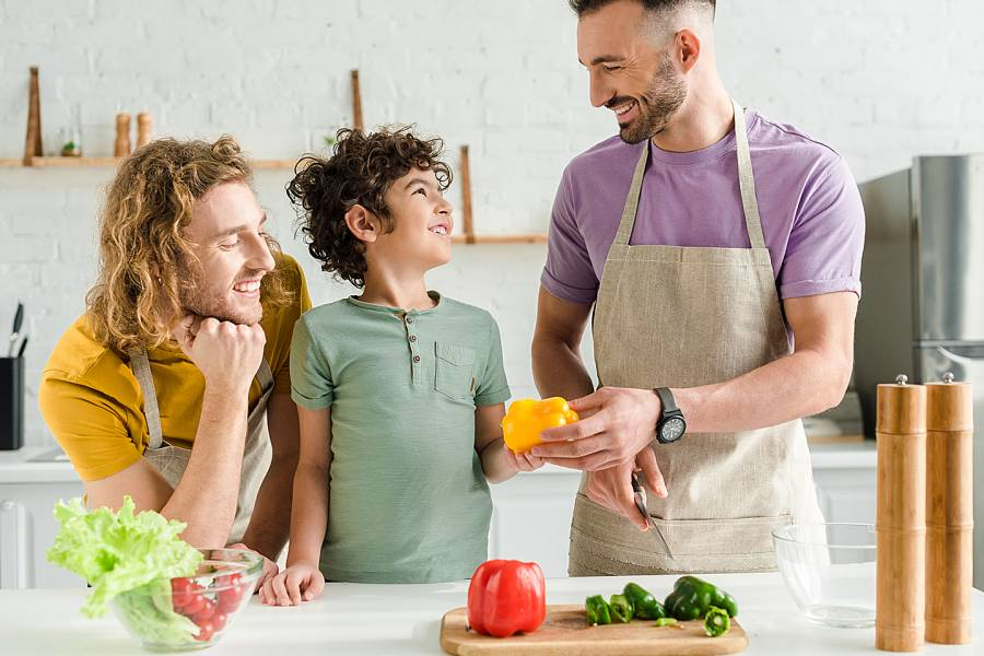 Two dads and their young son cutting up peppers in the kitchen