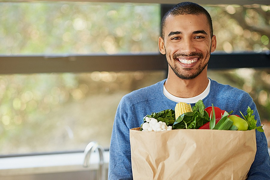 Photo of smiling man carrying a grocery bag of fresh vegetables.