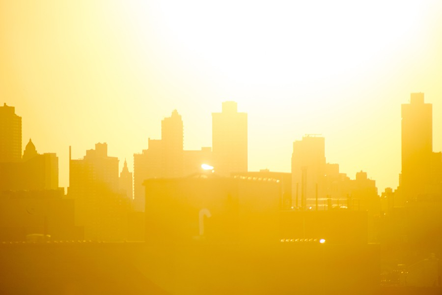City skyline silhouetted by blazing orange and yellow summer sun