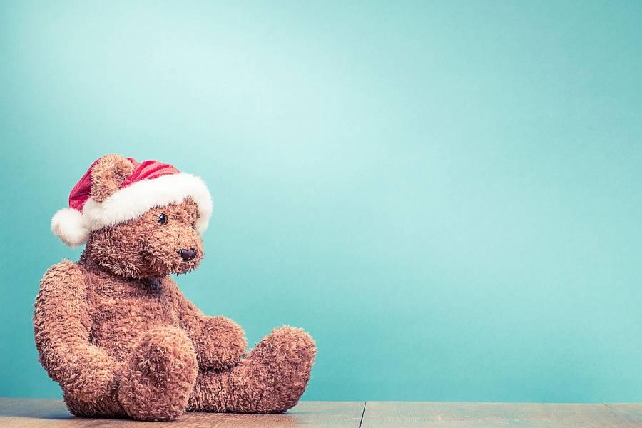 Sad-looking teddy bear wearing a Santa hat