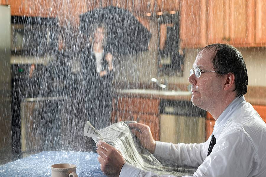 Man reading newspaper at kitchen table with water pouring through the ceiling. Woman in background is holding an umbrella.