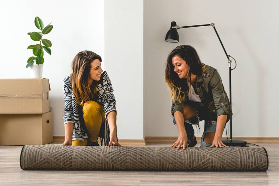 Two women unrolling a rug in their new apartment