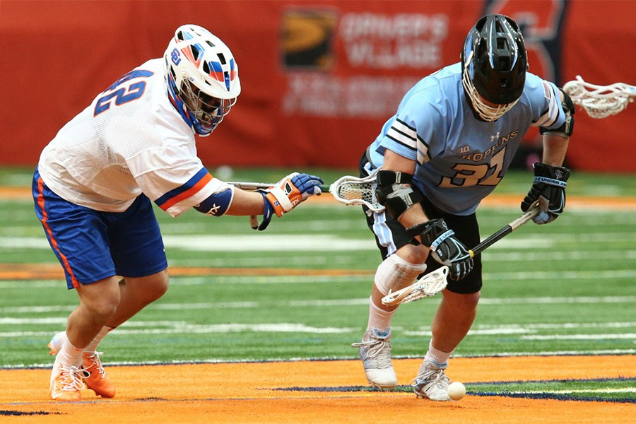 Two lacrosse players battle for a ground ball