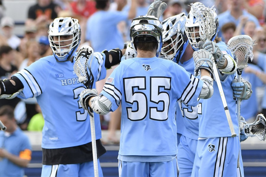 Four Hopkins lacrosse players celebrate a goal