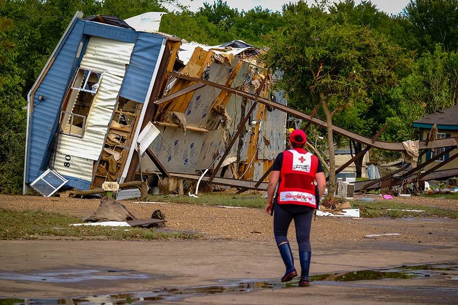 A trailer home lies on its side, having been ripped off its foundation, while a red cross volunteer looks on