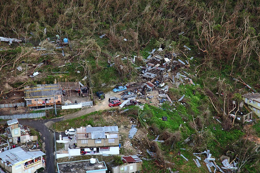 Homes lay in ruin in a rural and wooded area of Puerto Rico