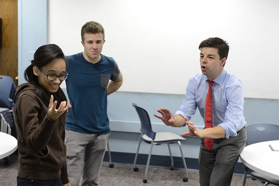A student holds something imaginary in her hand while the teacher coaches her through the scene