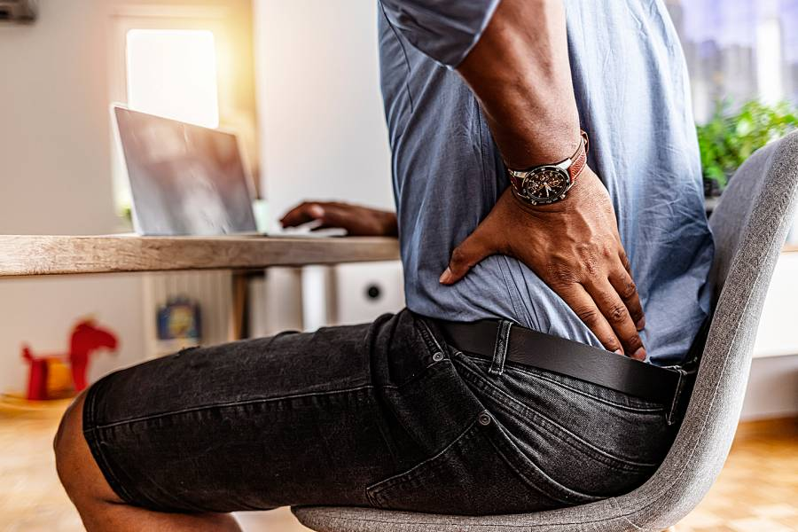 Man sitting at desk with hand on sore lower back