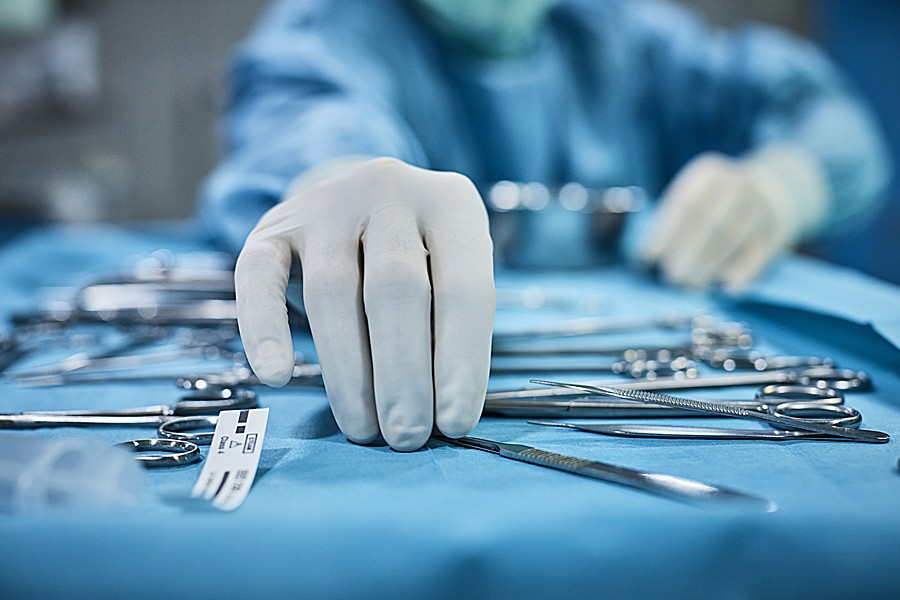 Gloved hand reaches for surgical instruments