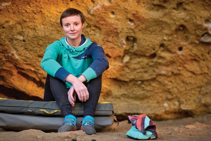 Inventor Jessamy Taylor sits in front of a boulder at Oregon's Smith Rock State Park