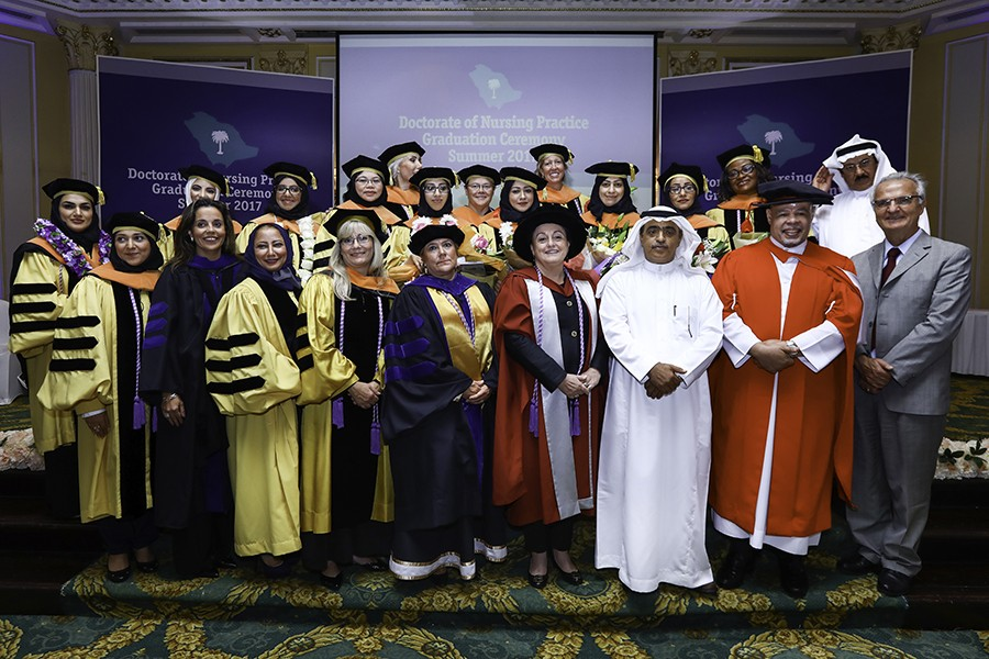 A group of people all wear graduation regalia, some of whom also wear traditional Saudi garbs