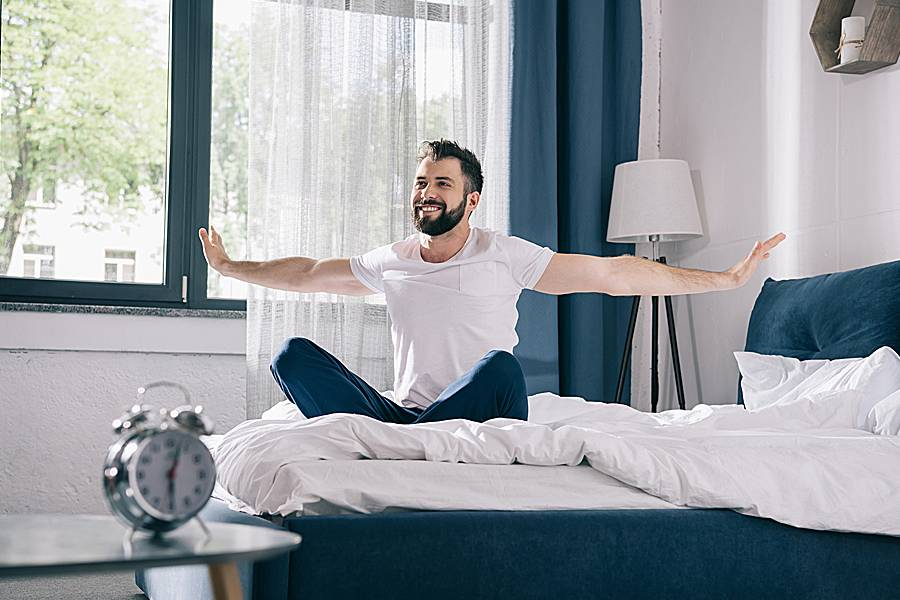Happy man stretching his arms when he wakes up