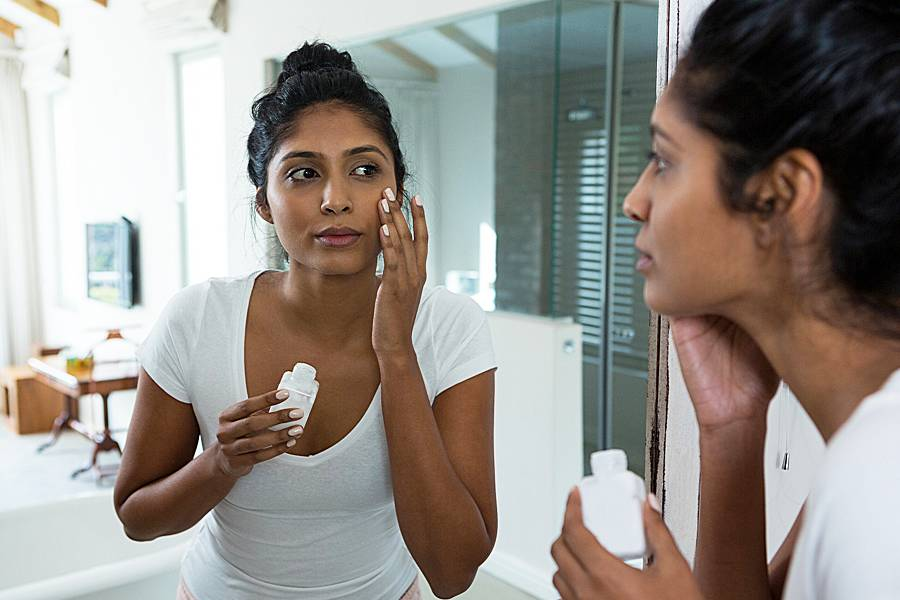Woman applies lotion to her face