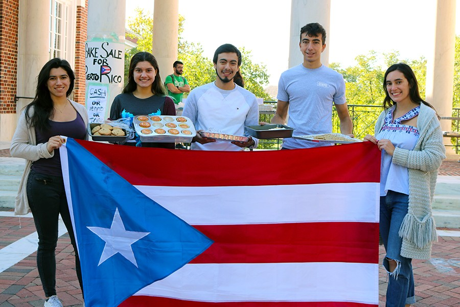 Puerto Rico JHU students hold Puerto Rican flag and trays of bakes goods.