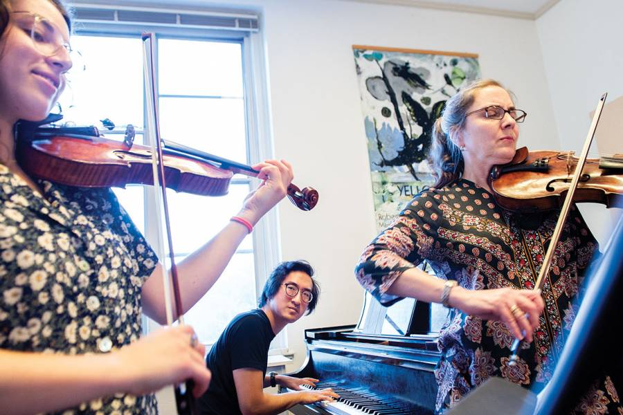 A violist, a violinist, and a pianist rehearse for a performance