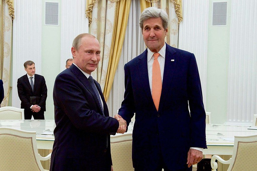 Vladimir Putin shakes the hand of John Kerry