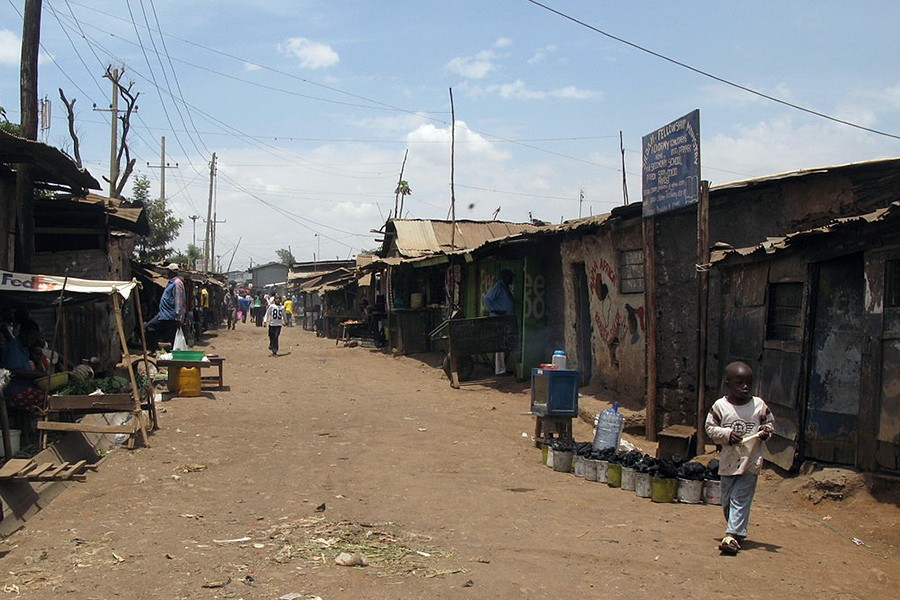 A main thoroughfare is a dirt road with corn debris littering the middle. Buildings are assembled with a mix of materials including cardboard, sheet metal, and trash including a FedEx sign