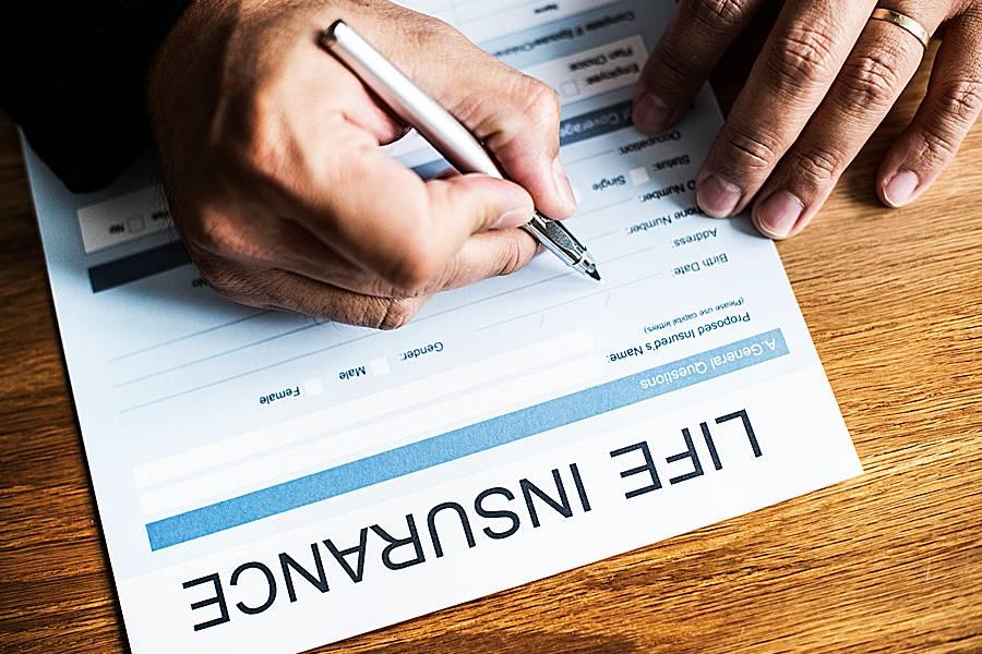 Man signing life insurance application