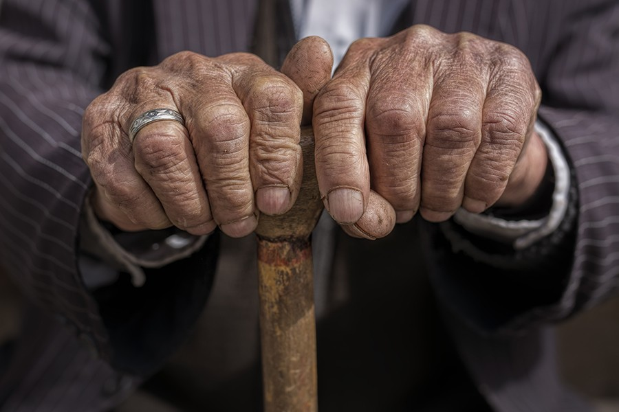 Close-up image of an old man holding a cane