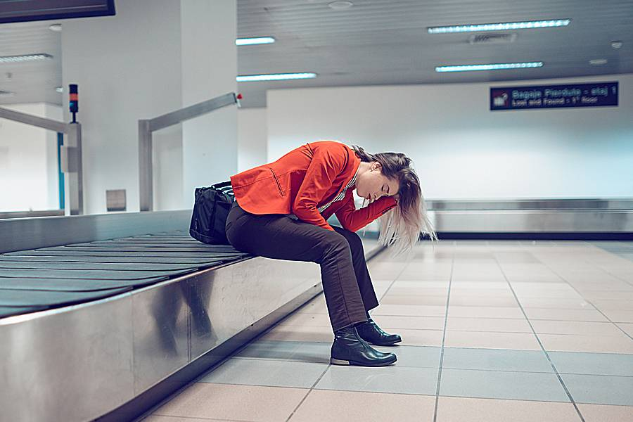 Frustrated woman sitting in the airport on an empty conveyer belt, having lost her luggage