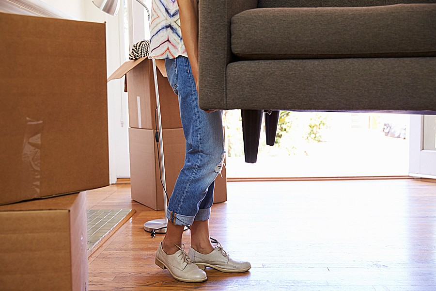 A woman carries one end of a couch into a room filled with moving boxes