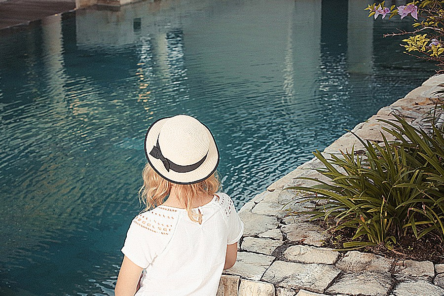 Photograph of a woman in a straw hat contemplating a peaceful-looking body of water