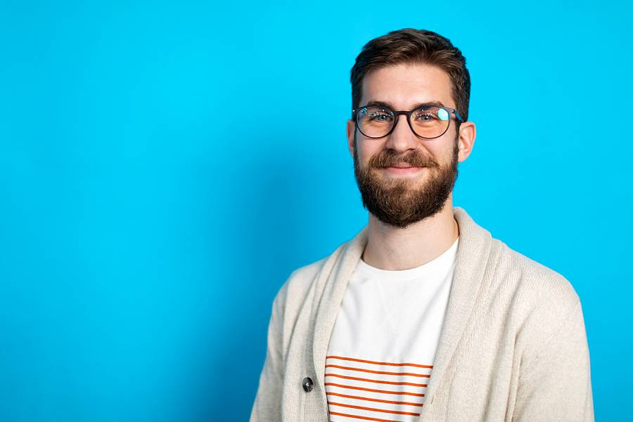 Smiling young male office worker with glasses and a beard