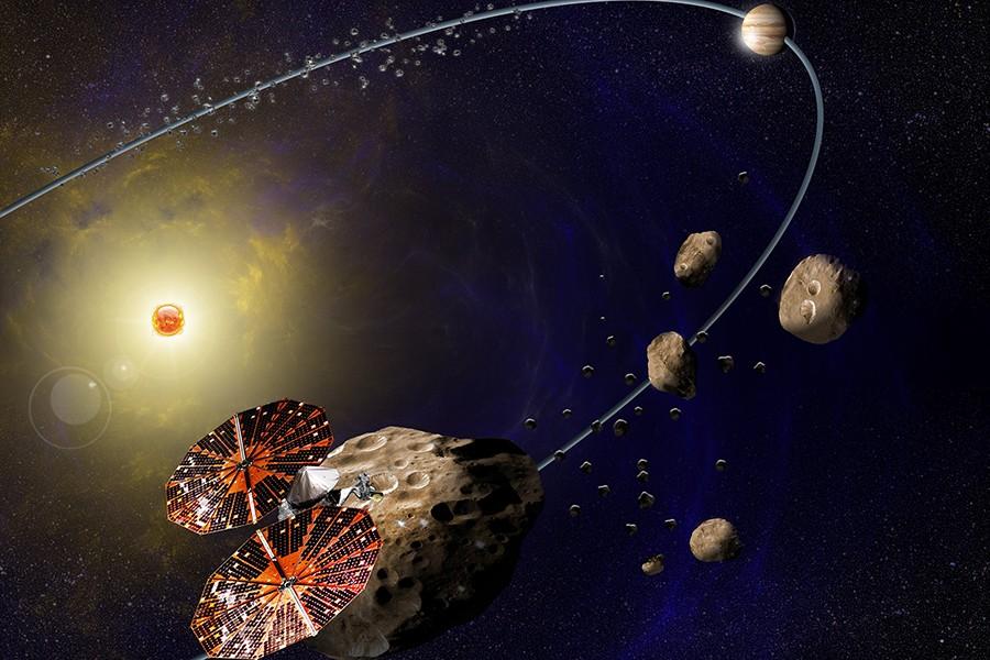 Spacecraft in bottom left corner flies past hunks of rock; in the top right, Jupiter is shown in its orbit around the sun