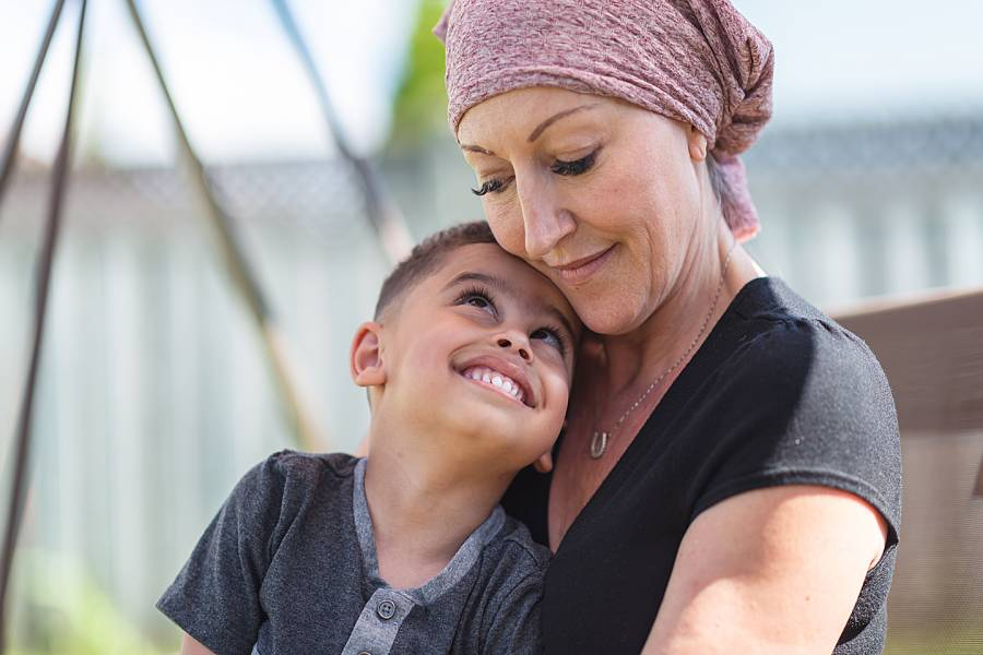 Serious-looking woman with head wrap holding her child