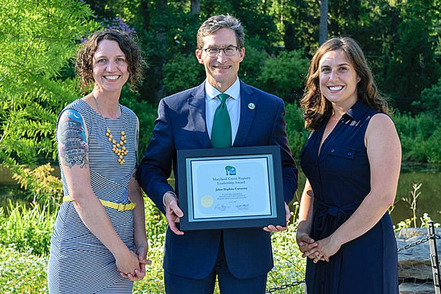 Homewood campus recycling manager Leana Houser and recycling manager Brigid Gregory receive the JHU award from Ben Grumbles, secretary of the Maryland Department of the Environment.