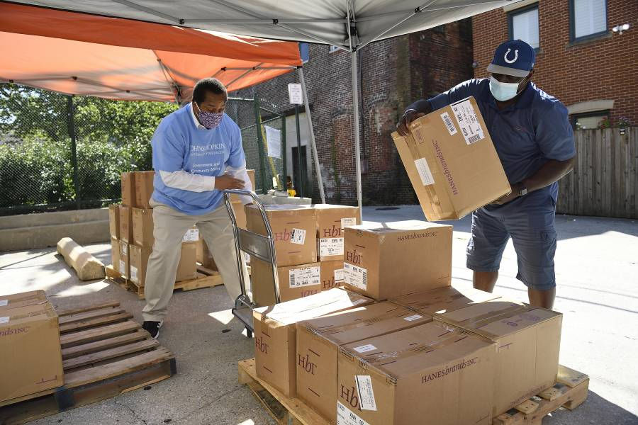 Volunteers load pallets with boxes of masks