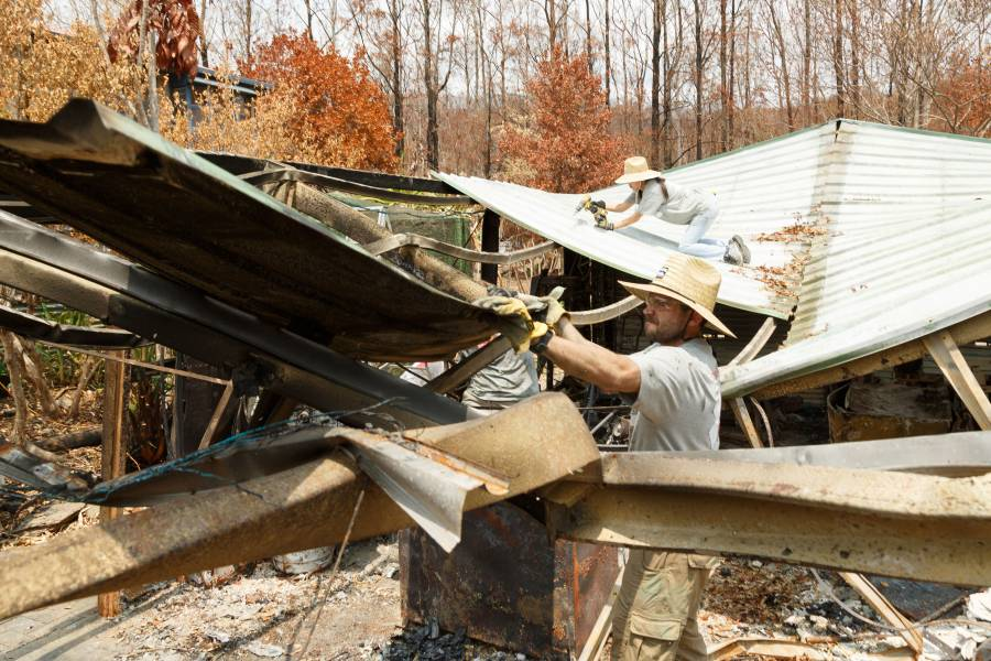 Alum William McNulty sorts through the rubble of a home destroyed by the Australian bush fires