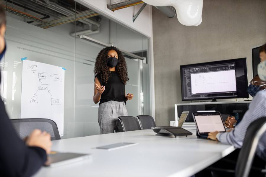 A masked woman presents in a business meeting