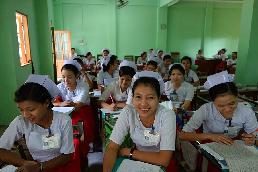 A group of midwives study in a classroom.