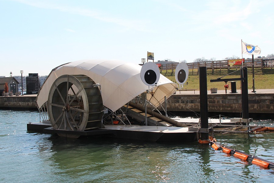 A wooden water wheel is covered with canvas and looks like a snail. Affixed to its cover are two large googly eyes to make it look even more like a snail.