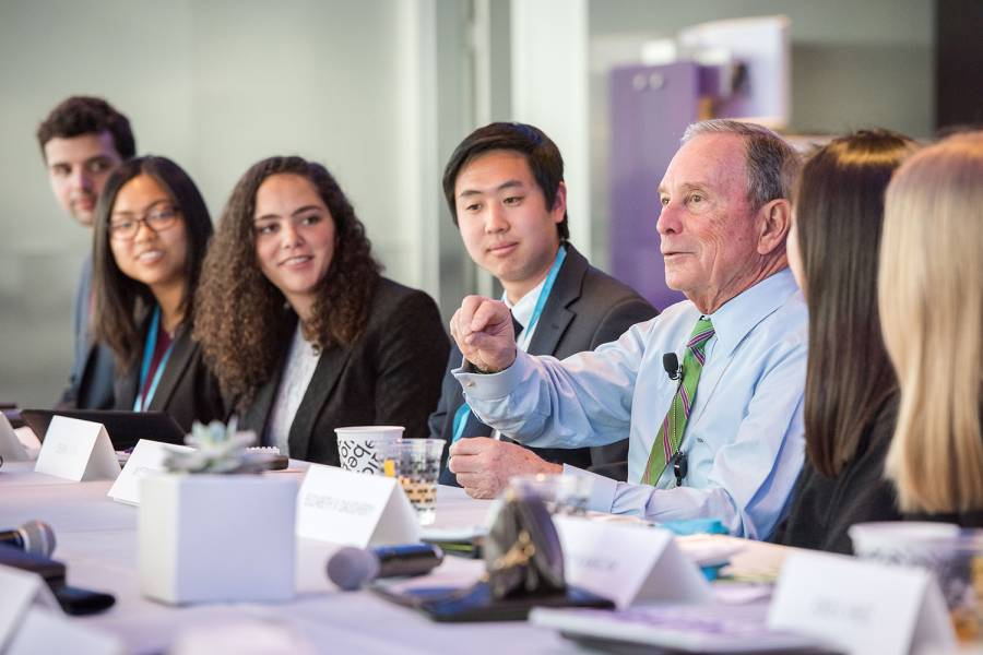 Michael R. Bloomberg seated a table with students