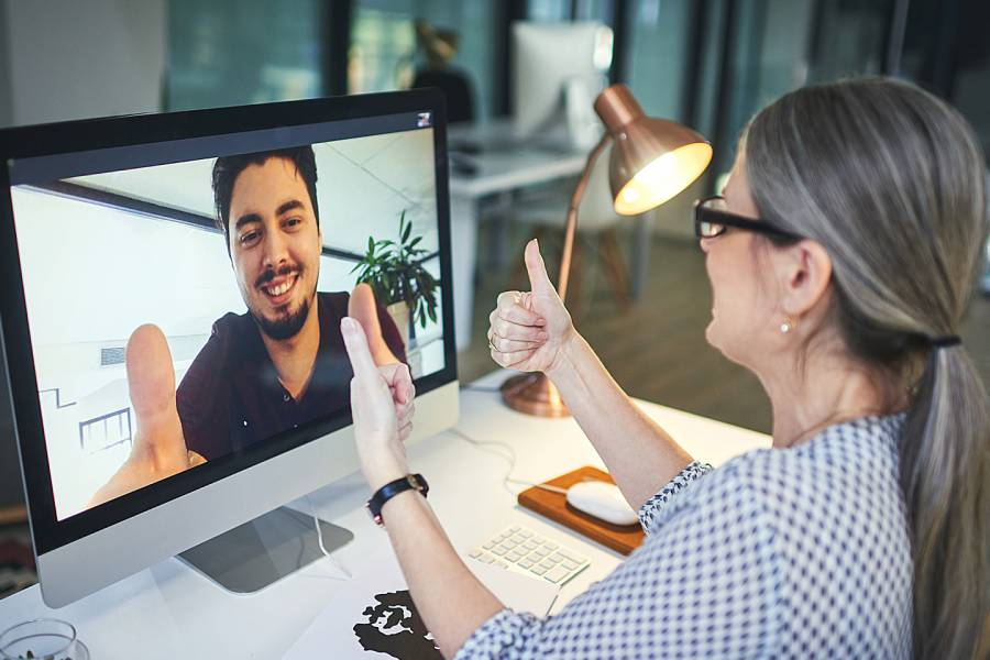 Counselor gives thumbs up to young man appearing on her computer screen