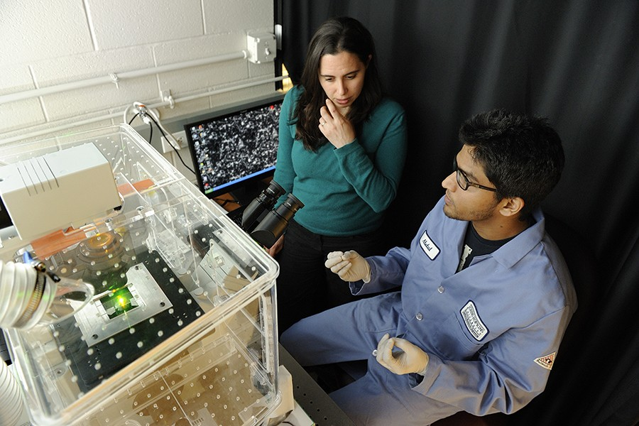 Researchers sit next to a a single-molecule fluorescence microscope