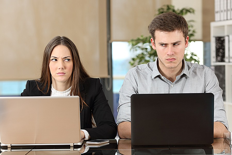 Female and male co-workers glare at each other while working side-by-side on their laptops.