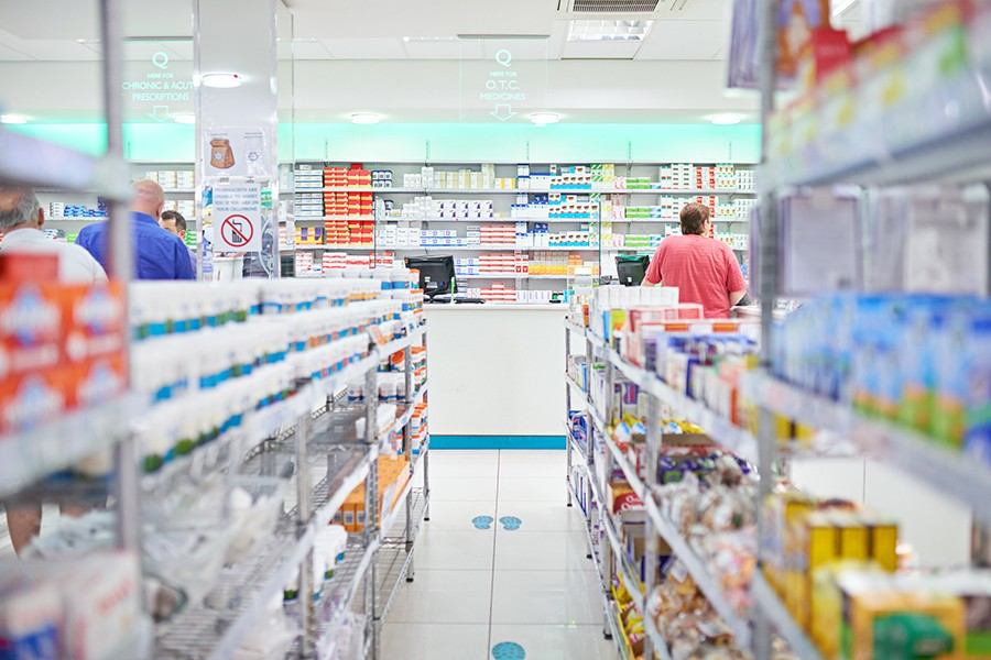 A customer stands in line at the pharmacy