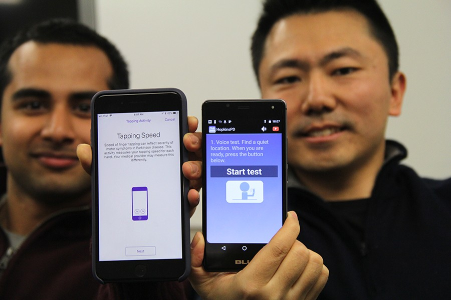 Two men hold up smartphones showing HopkinsPD app