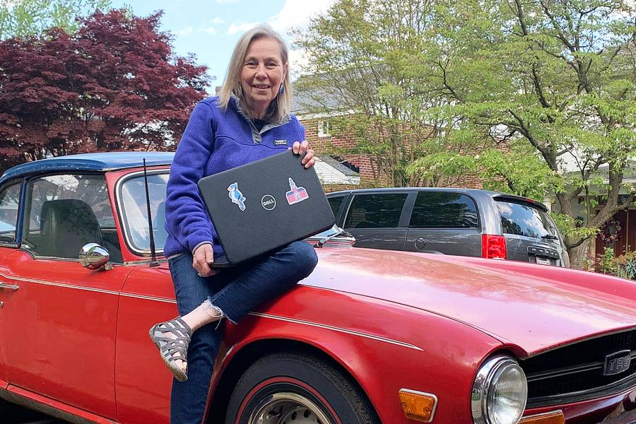 Pat Conklin sitting on the hood of an old sports car outside her home in Hamilton